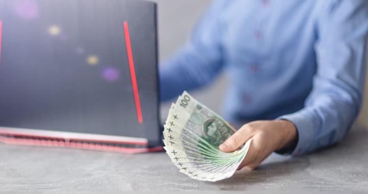 Oferta kredytowa, pożyczka. Polskie pieniądze trzymane przez bankowca w ręce.